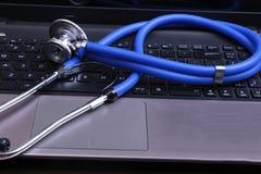 Μπλε ιατρικό στηθοσκόπιο σε έναν σκοτεινό φορητό προσωπικό υπολογιστή Στοκ Εικόνες