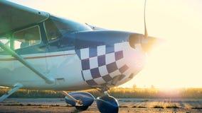 Μπλε και άσπρο biplane, αεροπλάνο, αεροπλάνο, αεριωθούμενο αεροπλάνο με έναν λειτουργώντας προωστήρα στις ακτίνες του ήλιου απόθεμα βίντεο