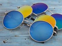 Μπλε και κίτρινα γυαλιά ηλίου σε ένα ξύλινο υπόβαθρο Στοκ εικόνα με δικαίωμα ελεύθερης χρήσης