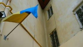 Μπλε και κίτρινοι ουκρανικοί κυματισμοί σημαιών στον τοίχο του κατοικημένου κτηρίου