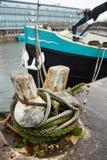 Μπλε και μαύρο σκάφος που ελλιμενίζεται σε μια σκουριασμένη πρόσδεση σιδήρου στοκ εικόνες με δικαίωμα ελεύθερης χρήσης