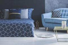 Μπλε καναπές στην άνετη κρεβατοκάμαρα Στοκ Εικόνες