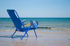 Μπλε καρέκλα παραλιών και μπλε καπέλο στο καλοκαίρι μπλε ουρανού ακτών Στοκ Εικόνες