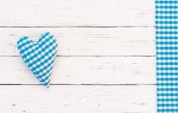Μπλε καρδιά υφάσματος στο άσπρο ξύλο με τα μπλε ελεγχμένα σύνορα Στοκ Εικόνες