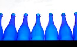 Μπλε κενά μπουκάλια που παρατάσσονται σε έναν μετρητή στοκ εικόνες