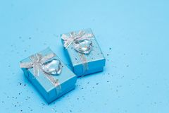 Μπλε κιβώτιο δώρων με το κόσμημα και την καρδιά κρυστάλλου, γύρω από τα τσέκια Μπλε υπόβαθρο στοκ εικόνες