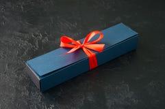 Μπλε κιβώτιο δώρων με το κώλυμα με τη σοκολάτα σε μια μαύρη πλάτη πετρών Στοκ Εικόνα