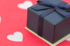 Μπλε κιβώτιο δώρων με το σύνολο υποβάθρου των άσπρων καρδιών στο κόκκινο στοκ εικόνα
