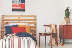 Μπλε, κόκκινα και πορτοκαλιά μαξιλάρια στο ενιαίο κρεβάτι με γδυμένος duvet και ξύλινο headboard στην εσωτερική, πραγματική φωτογ στοκ εικόνες