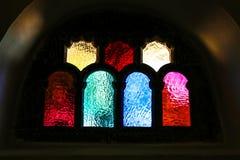 Μπλε, κόκκινα, πορφυρά και κίτρινα stained-glass παράθυρα και τα έντονα φω'τα στους τοίχους Στοκ Εικόνες