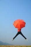 μπλε κόκκινος ουρανός άλματος στη γυναίκα ομπρελών Στοκ Φωτογραφία