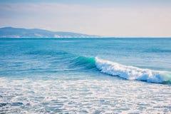 Μπλε κύματα που σπάζουν σε έναν σκόπελο κατά μήκος της ακτής της Ινδονησίας Στοκ Εικόνες
