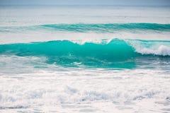 Μπλε κύματα που σπάζουν σε έναν σκόπελο κατά μήκος της ακτής της Ινδονησίας Στοκ Φωτογραφίες