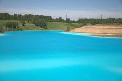 Μπλε λίμνη με τις υψηλές αμμώδεις ακτές που εισβάλλονται με το κωνοφόρο δασικό τοπίο στοκ εικόνα