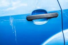 Μπλε λαβή πορτών αυτοκινήτων και γρατσουνισμένο χρώμα αυτοκινήτων με τις μειώσεις πουλιών Στοκ Φωτογραφία
