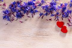 Μπλε λουλούδια και καρδιές στο ξύλο στοκ εικόνα