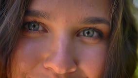 Μπλε μάτια του νέου καυκάσιου κοριτσιού brunette, που φαίνονται κεκλεισμένων των θυρών απόθεμα βίντεο