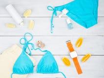 μπλε μαγιό, κίτρινα σορτς, έξυπνο ρολόι, sunscreen, λεμόνι και στοκ φωτογραφίες