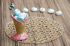 Μπλε μαρέγκα στο ρόδινο κώνο με τα cupcakes στο χαλί θέσεων, το ξύλινο υπόβαθρο και τις άσπρες μαρέγκες, ευτυχής ημέρα μητέρων στοκ εικόνα