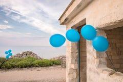 Μπλε μπαλόνια με το σπίτι στοκ εικόνα