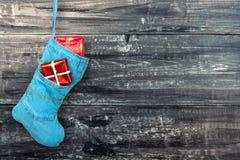 Μπλε μπότα Χριστουγέννων με τα δώρα στο ξύλινο υπόβαθρο Στοκ φωτογραφία με δικαίωμα ελεύθερης χρήσης