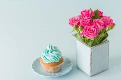 Μπλε οριζόντιο έμβλημα κρητιδογραφιών με τη τοπ άποψη διακοσμημένος με την μπλε κρέμα cupcake και τα ρόδινα τριαντάφυλλα στο αναδ Στοκ Εικόνα