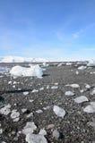 Μπλε ουρανοί με τα χοντρά κομμάτια των παγετώνων σε μια μαύρη στρωμένη με άμμο παραλία στοκ φωτογραφία με δικαίωμα ελεύθερης χρήσης