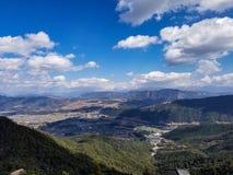 Μπλε ουρανός, άσπρα σύννεφα και βουνά στοκ εικόνες