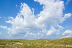 Μπλε ουρανός βουνών με τα άσπρα σύννεφα επάνω από τον πράσινο τομέα λόφων Στοκ Φωτογραφίες