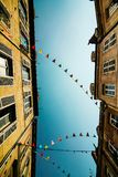 Μπλε ουρανός και σημαίες μεταξύ των σπιτιών Στοκ Φωτογραφίες