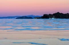 Μπλε πάγος Baikal της λίμνης κάτω από το ρόδινο ουρανό ηλιοβασιλέματος στοκ φωτογραφία
