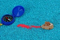 Μπλε παιχνίδι πυξίδων και βαρκών στο μπλε αμμοχάλικο στοκ εικόνα με δικαίωμα ελεύθερης χρήσης