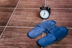 Μπλε παντόφλες και ξυπνητήρι Ώρα για ύπνο r στοκ εικόνες