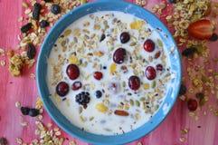 Μπλε πιάτο στο ρόδινο σύνολο πινάκων Oatmeal, των σπόρων chia, των φρέσκων μούρων, των σπόρων, των καρυδιών και του γάλακτος στοκ φωτογραφία με δικαίωμα ελεύθερης χρήσης
