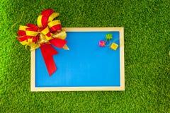 Μπλε πλαίσιο φωτογραφιών με την κορδέλλα και το μικρό ζωηρόχρωμο κιβώτιο του δώρου στο γ Στοκ Φωτογραφία