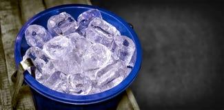 Μπλε πλαστικός κάδος που γεμίζουν με τα χοντρά κομμάτια του πάγου με θολωμένο Backg Στοκ Εικόνες