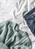 Μπλε πλεκτά πουλόβερ και τζιν γυναικών ` s στο κρεβάτι, τοπ άποψη ελεύθερου χώρου Στοκ Εικόνες