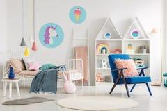 Μπλε πολυθρόνα δίπλα στο κρεβάτι με το κάλυμμα στο ζωηρόχρωμο bedro παιδιών ` s Στοκ Εικόνες