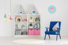 Μπλε πολυθρόνα στο εσωτερικό δωματίων έξυπνων, παιδιών ` s scandi με το colorfu Στοκ Φωτογραφία