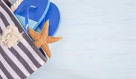 Μπλε πτώσεις κτυπήματος στην τσάντα και τον αστερία παραλιών στο ανοικτό μπλε backgrou Στοκ φωτογραφίες με δικαίωμα ελεύθερης χρήσης