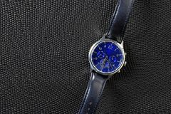 Μπλε ρολόι με το λουρί δέρματος πέρα από το μαύρο διαμορφωμένο δέρμα σαυρών στοκ εικόνα με δικαίωμα ελεύθερης χρήσης