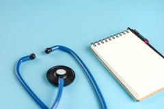 Μπλε στηθοσκόπιο και ένα σημειωματάριο σε ένα μπλε υπόβαθρο στοκ εικόνες