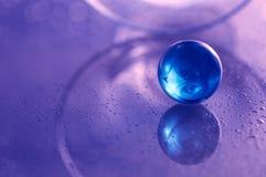Μπλε σφαίρα γυαλιού σε έναν άσπρο πίνακα γυαλιού Αφηρημένη φωτογραφία με το γυαλί και την αντανάκλαση Εκλεκτική εστίαση Στοκ Εικόνες