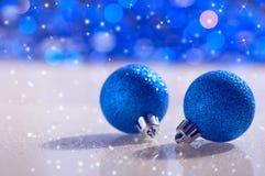 Μπλε σφαίρες Χριστουγέννων στο αφηρημένο υπόβαθρο με το bokeh και snowflakes Στοκ Εικόνες