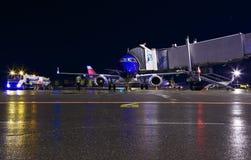 Μπλε σύγχρονος αερολιμένας νύχτας συντήρησης αεροσκαφών, φορτηγό καυσίμων, αεριωθούμενη γέφυρα και οι άνθρωποι προσωπικού Απολύτω Στοκ φωτογραφία με δικαίωμα ελεύθερης χρήσης