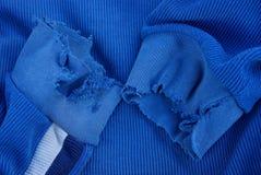 Μπλε σύσταση υφάσματος με τα σχισμένα μανίκια στα παλαιά ενδύματα στοκ εικόνες