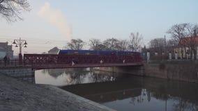 Μπλε τραίνο και άνθρωποι στην κόκκινη γέφυρα που οδηγεί σε Ostrow Tumski απόθεμα βίντεο