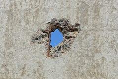 Μπλε τρύπα στον παλαιό γκρίζο συμπαγή τοίχο ενός φράκτη στοκ εικόνες