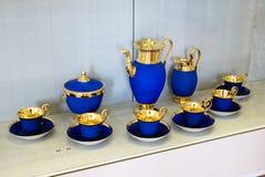 Μπλε τσάι πορσελάνης πολυτέλειας που τίθεται με τη χρυσή περιποίηση φύλλων στοκ φωτογραφίες