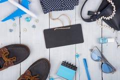 μπλε τσάντα, γυαλιά ηλίου, παπούτσια, στιλβωτική ουσία καρφιών, κενός πίνακας, σημειωματάριο και λίγο αεροπλάνο στο άσπρο ξύλινο  Στοκ φωτογραφίες με δικαίωμα ελεύθερης χρήσης